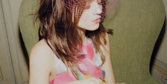 Miniabito di seta, Emporio Armani. Cappellino con piume e veletta, Grevi. Anelli d'oro rosa con topazio e quarzo, Pomellato. In tutto il servizio: anelli d'oro a scaglie con pietre colorate, Giovanni Raspini